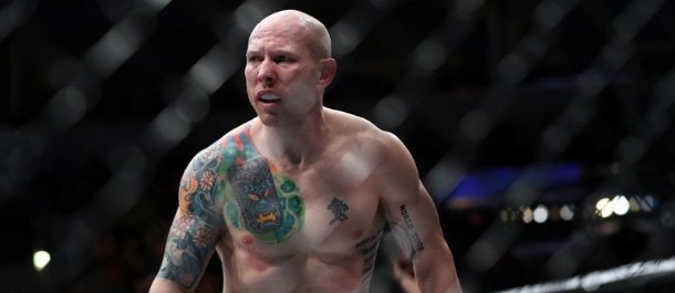 Josh Emmett walks around the cage after winning by KO